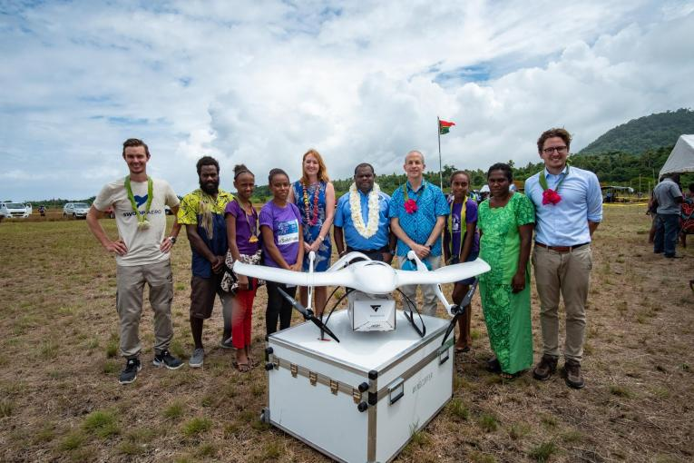 Group of people standing by Wingcopter Drone in Vanuatu delivering vaccines for Unicef
